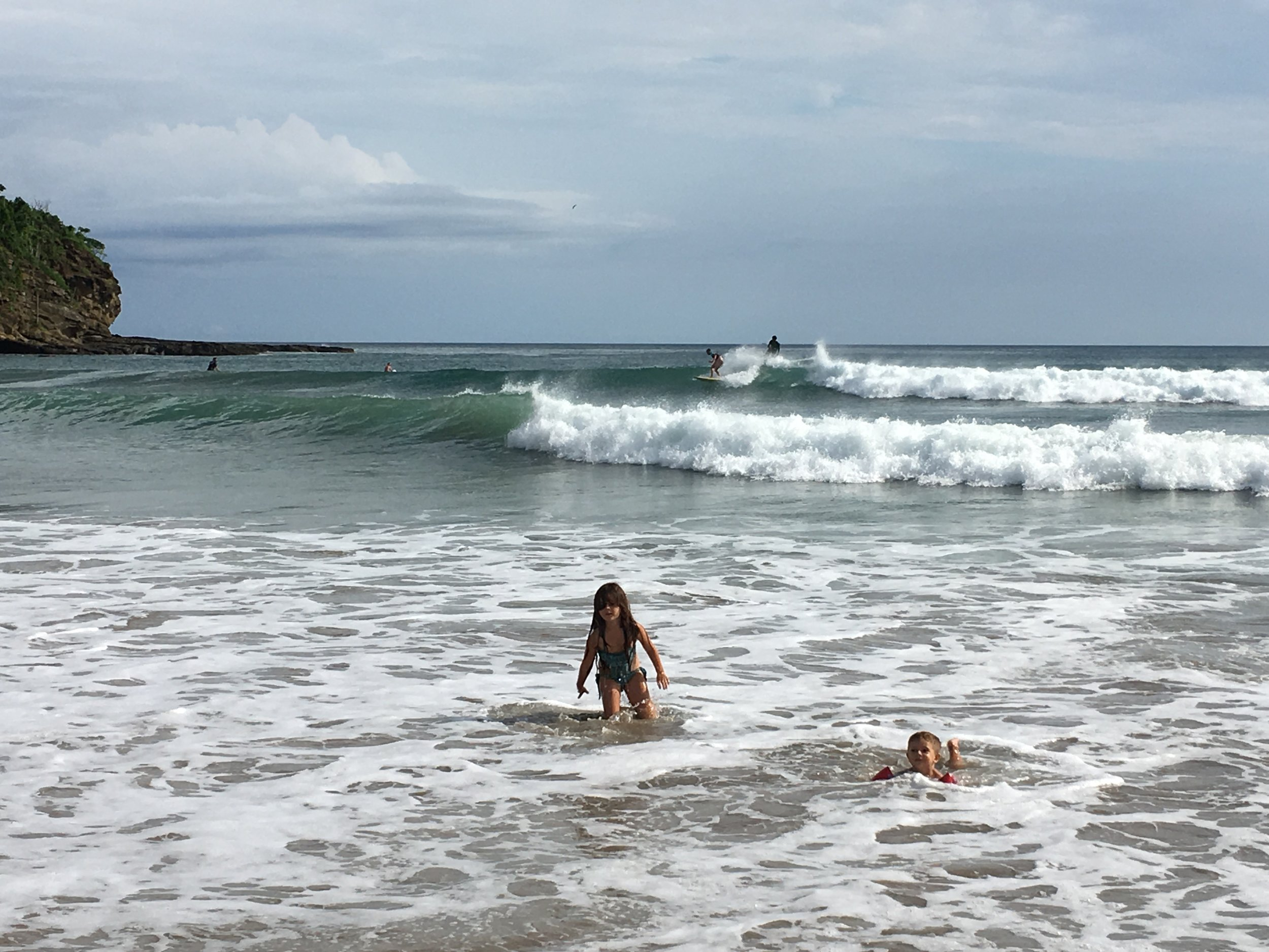 Surfers catching waves and children wading close to shore